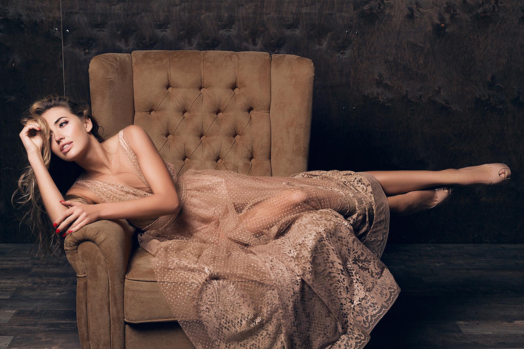 Kobieta w eleganckiej beżowej sukience, ilustracja do artykułu o butach pasujących do beżowej sukienki